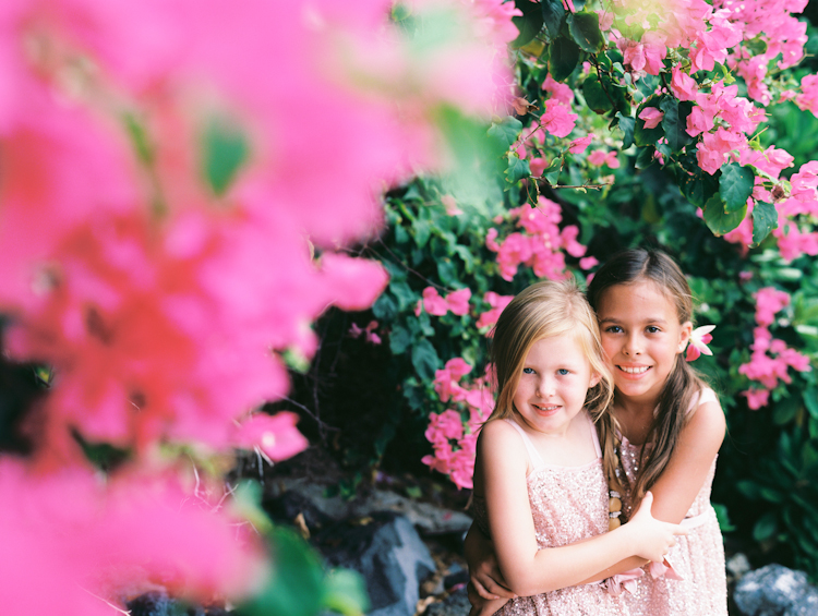 maui photographer wendy laurel's image of two sisters hugging in pink bush