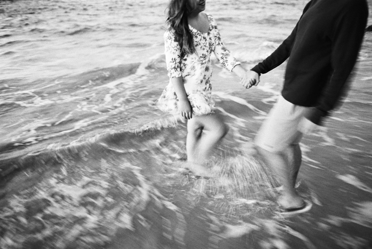 maui wedding photographer wendy laurel's black and white image of girl and guy kissing in ocean