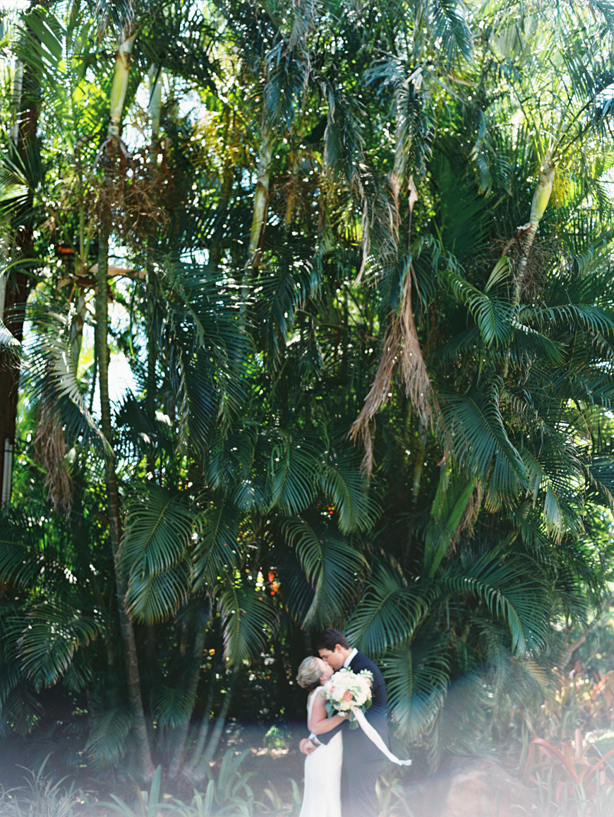 tiny bride and groom against palm leaf backdrop by wendy laurel