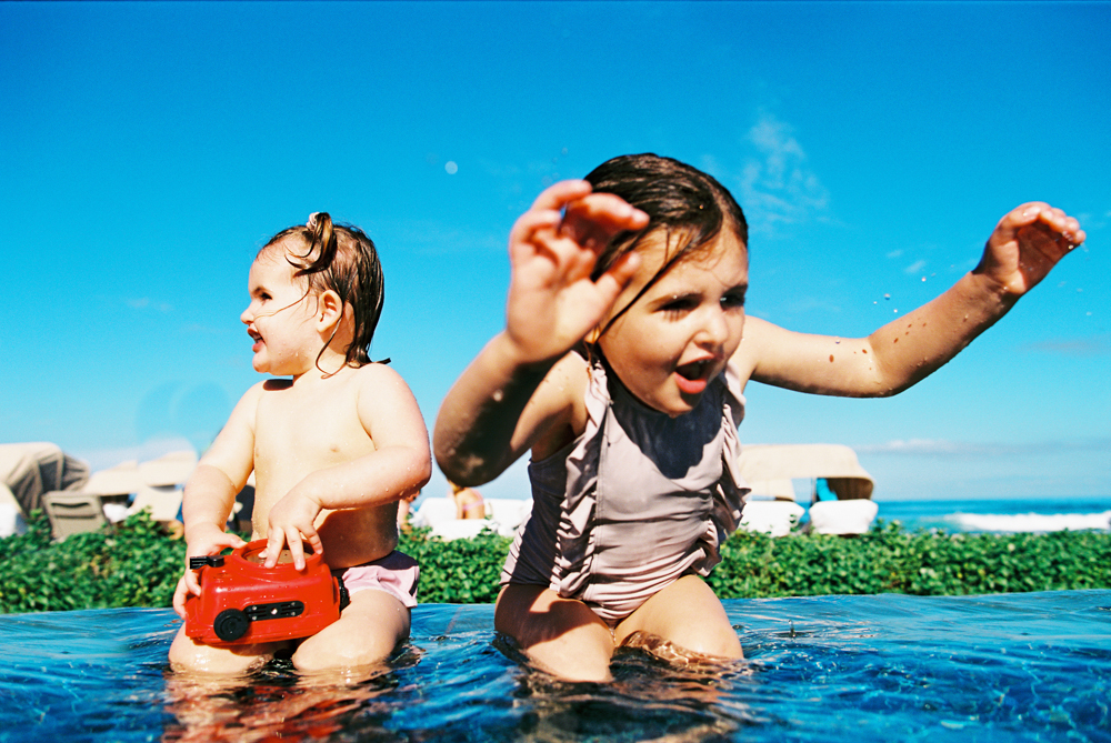 film photo of two girls at four seasons kona jumping in pool by wendy laurel