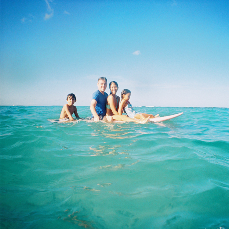 maui photographer wendy laurel's photographs of hawaii family in ocean with surfboards with film cameras in waikiki-1
