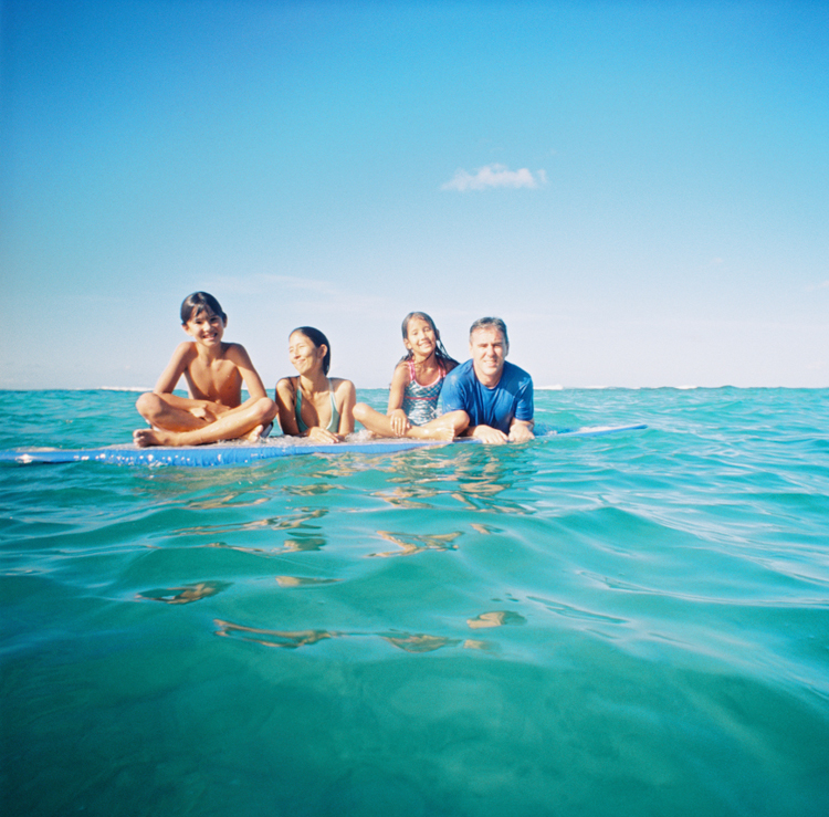 maui photographer wendy laurel's water image of family in ocean on surfboard