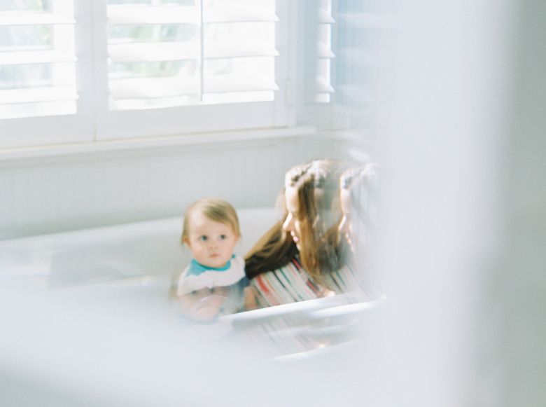 mom and baby in white tub mirror reflect image by photographer wendy laurel