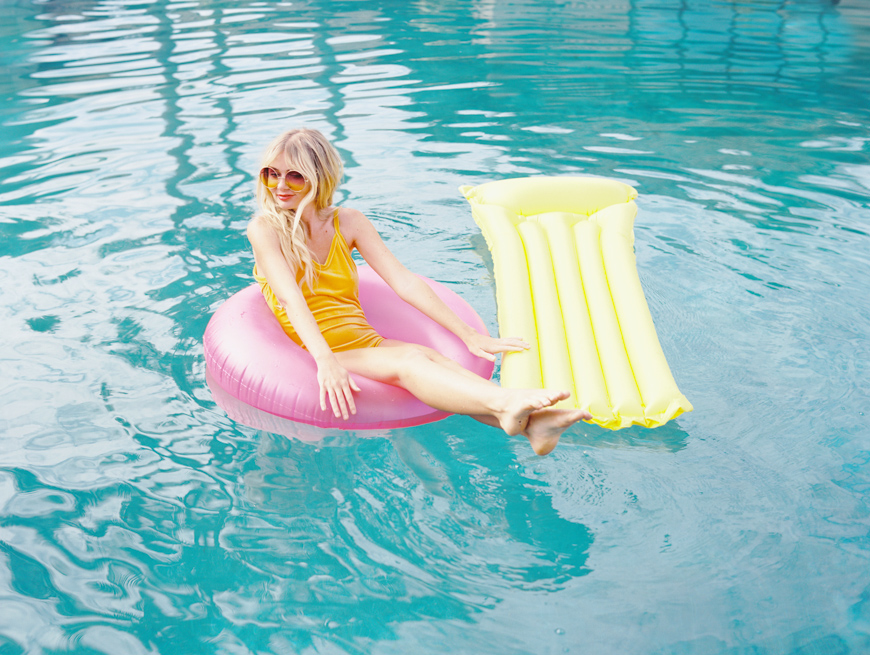 wendy laurel photo of girl in pool with colored rafts