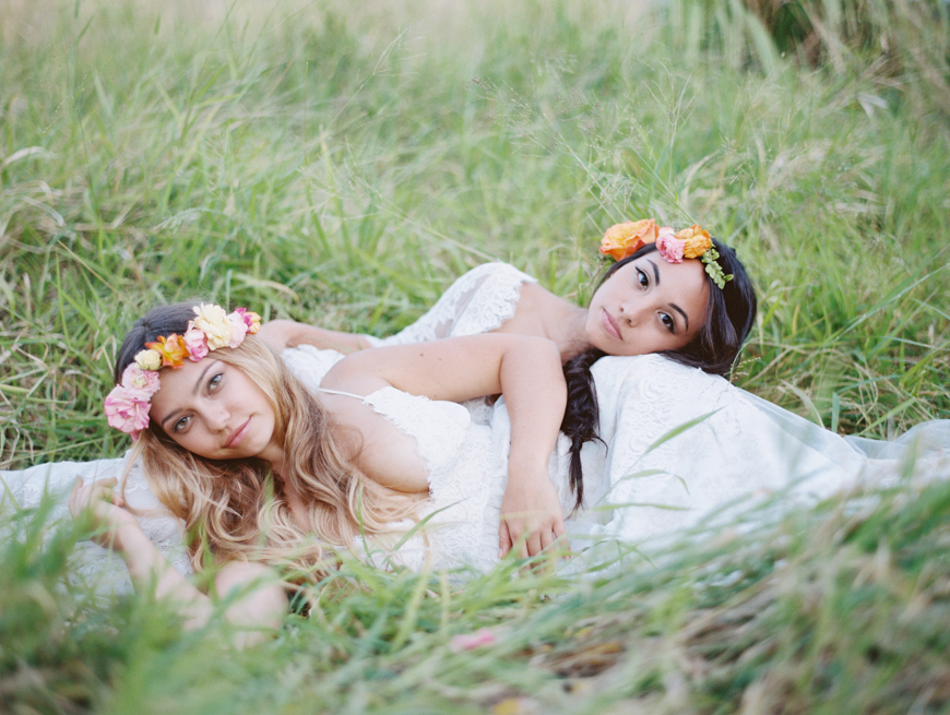 beautiful brides laying on each other in field