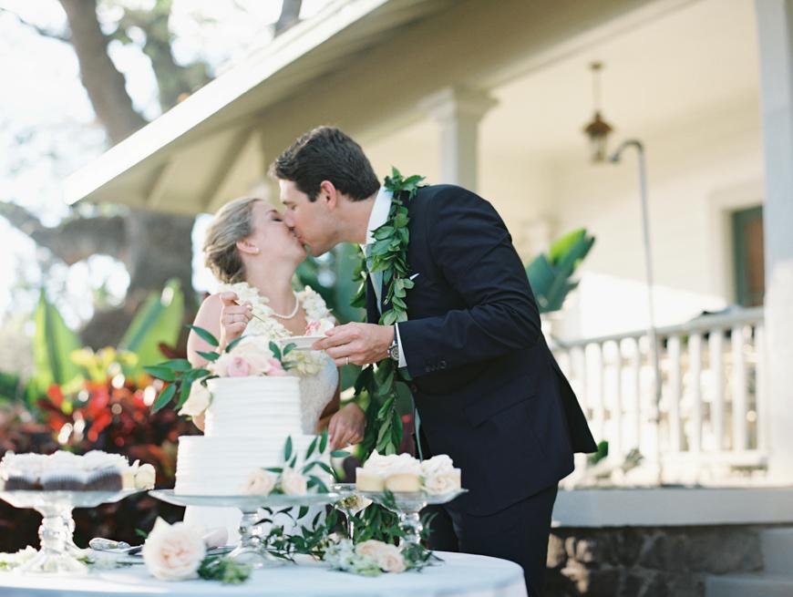 bride and groom kissing at cake by wendy laurel