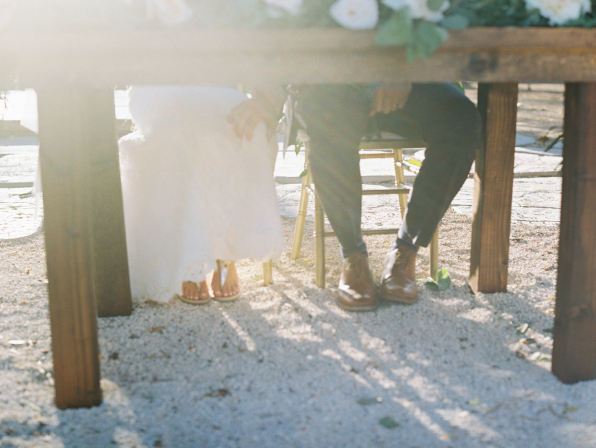 bride and groom touching under table at olowalu plantation house reception