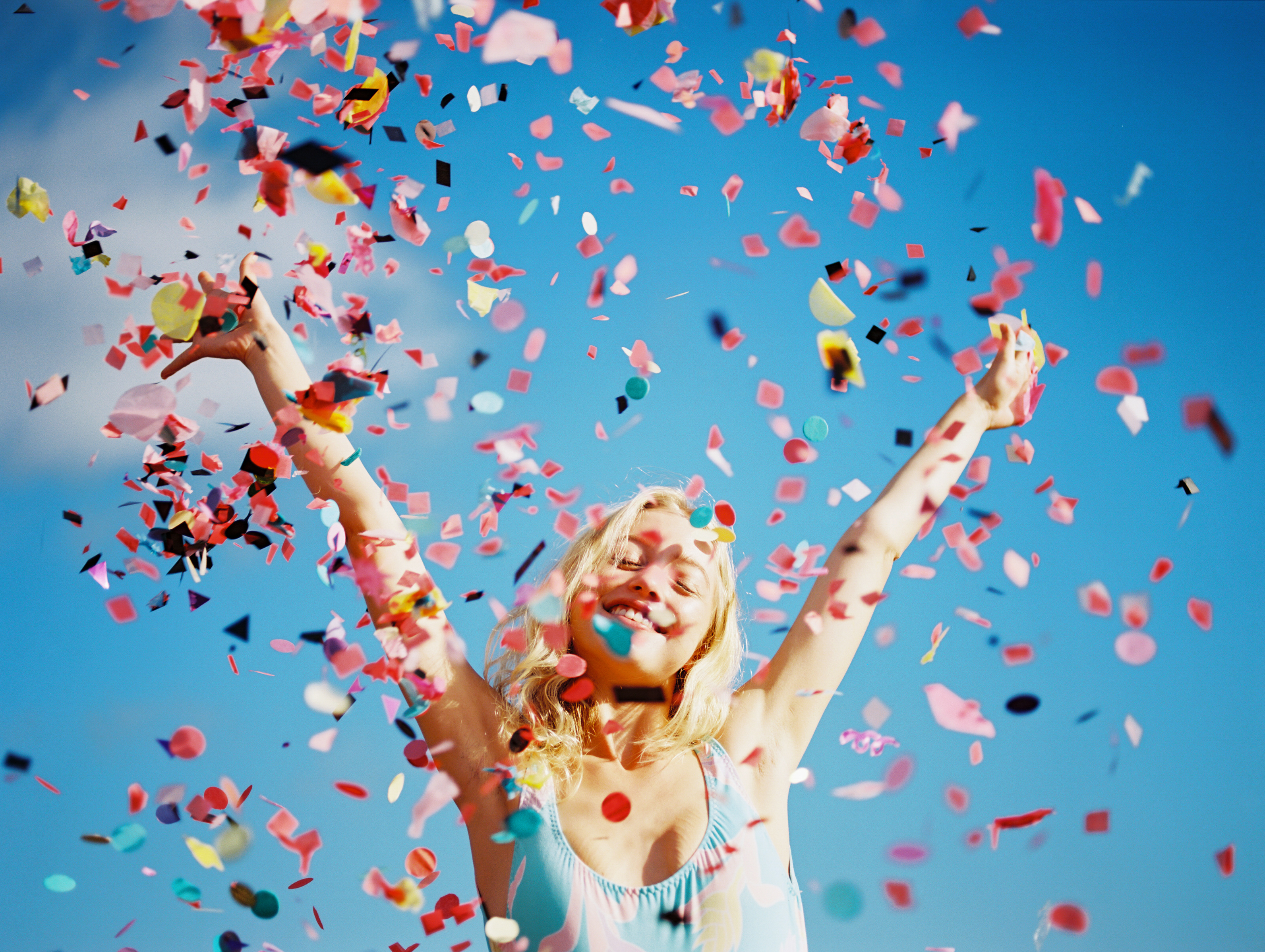 hawaii girl with colored confetti against bright blue sky by maui photographer wendy laurel