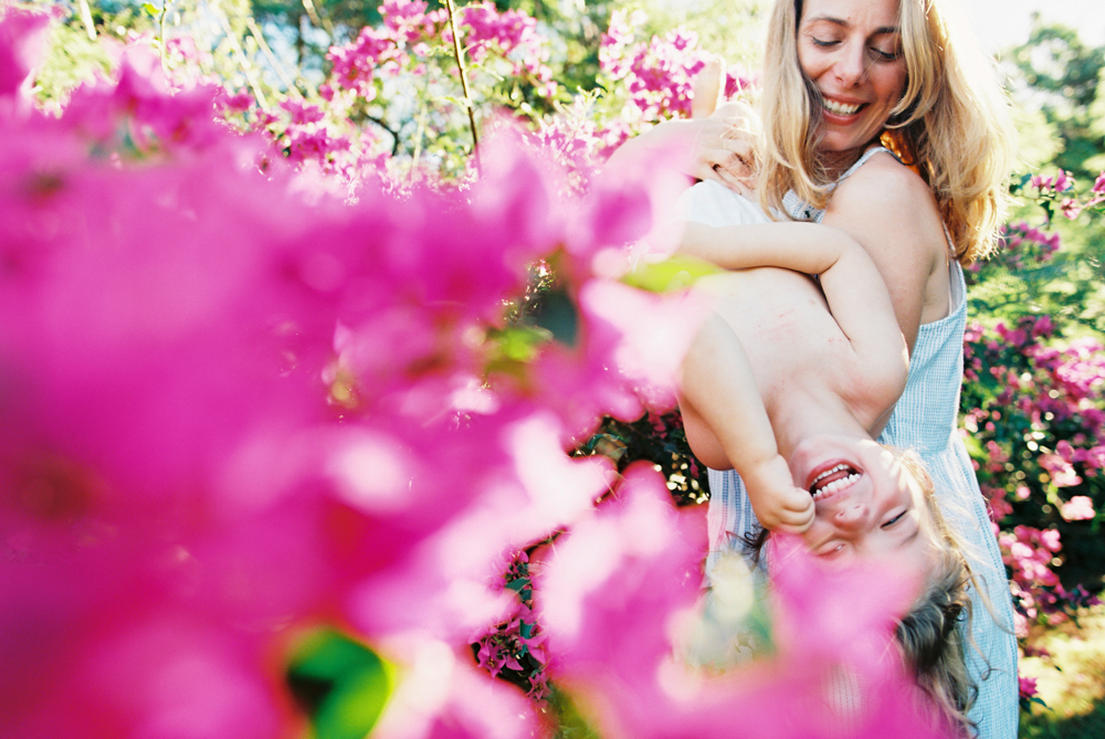 mom and daughter smiling in pink bougainvllea by maui photographer wendy laurel