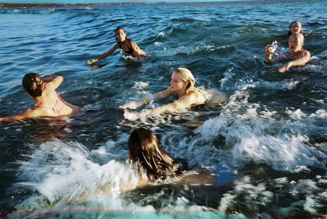 teenage girls swimming in ocean by maui photographer wendy laurel