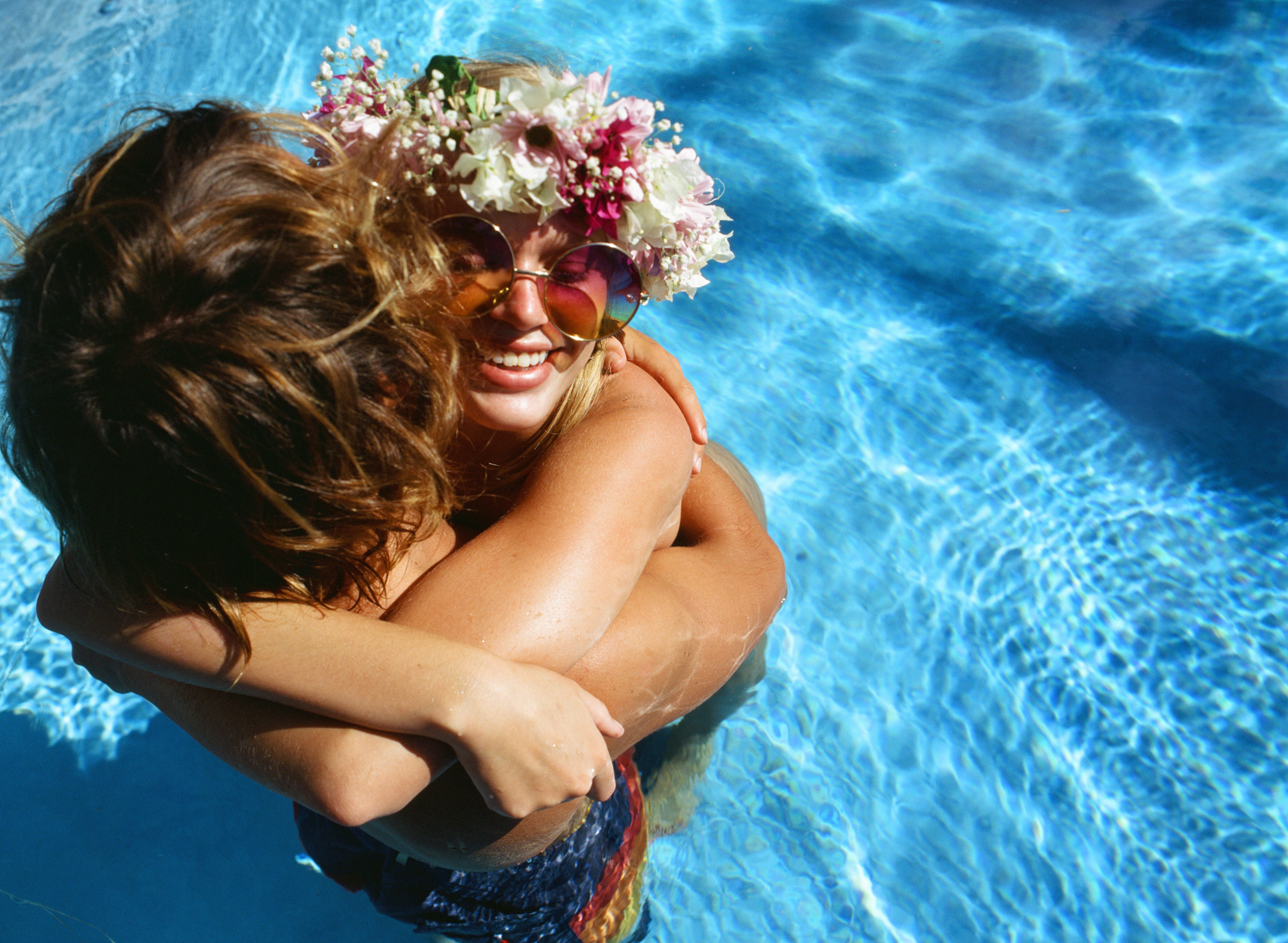 Boho couple in pool with flower headband by maui family photographer wendy laurel