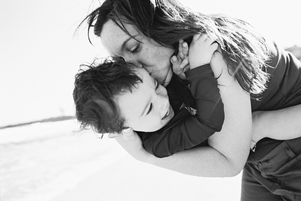 mom kissing young son at ironwoods beach by wendy laurel