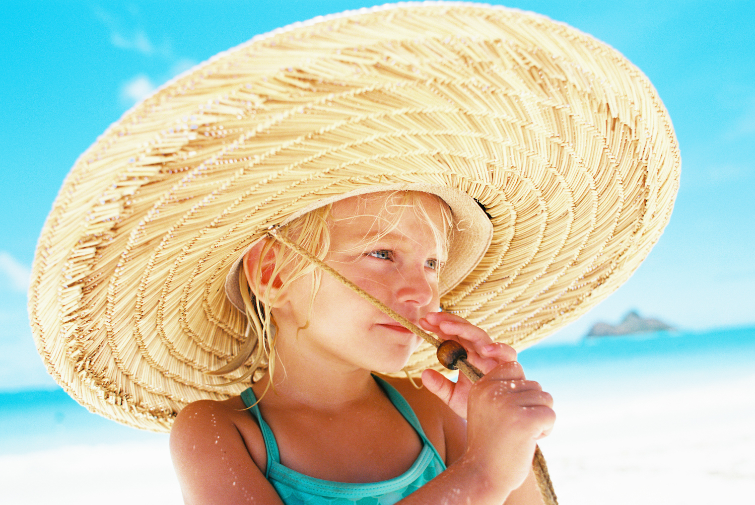 girl in beach hat at lanikai by photographer wendy laurel